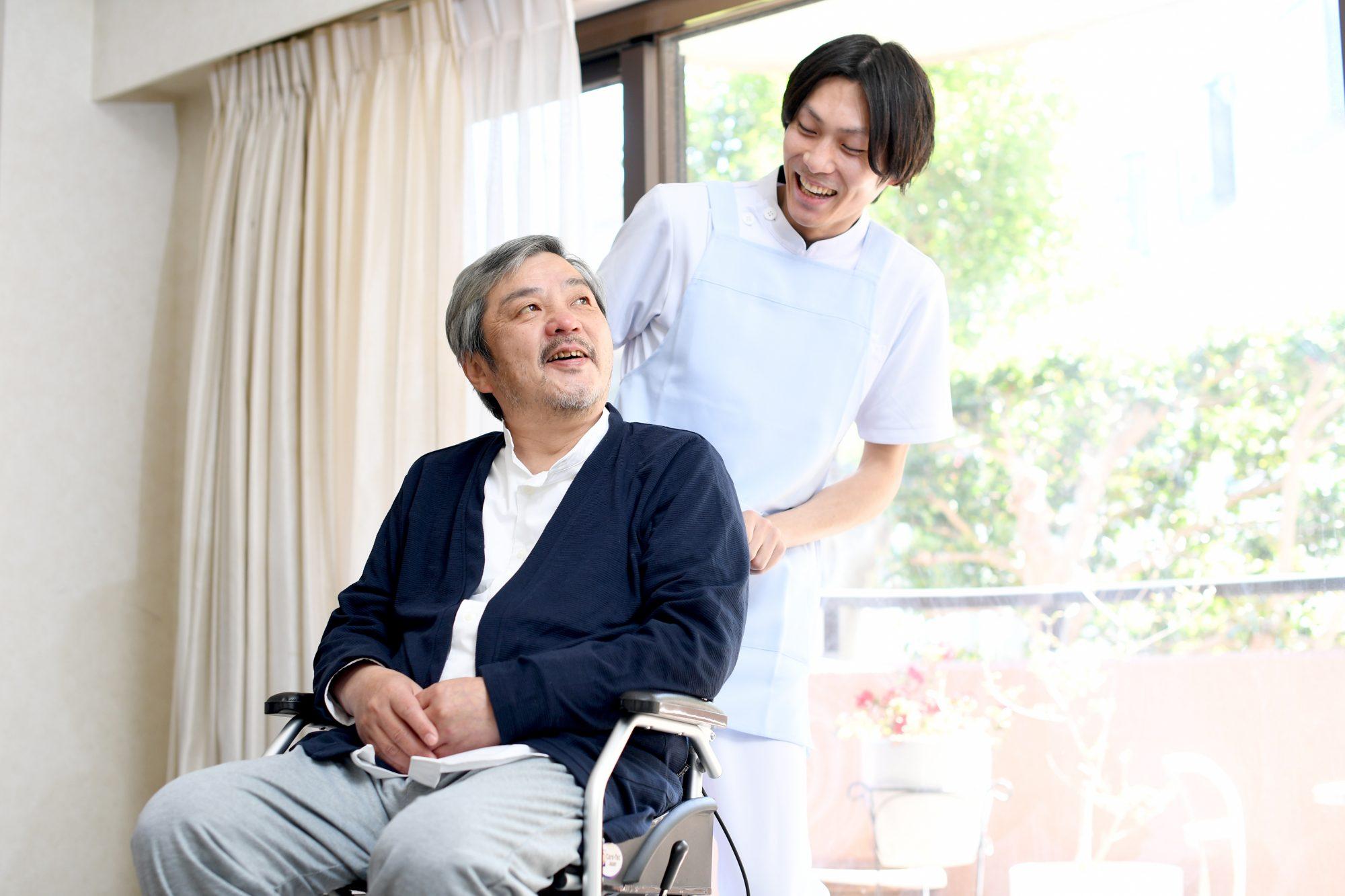 車椅子を押す男性介護士と笑顔のシニア男性
