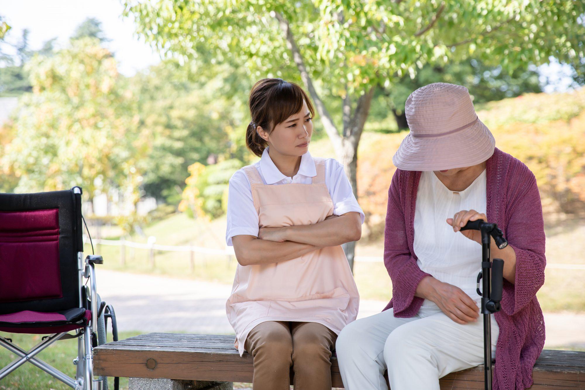 腕を組む介護士とうつむく老人