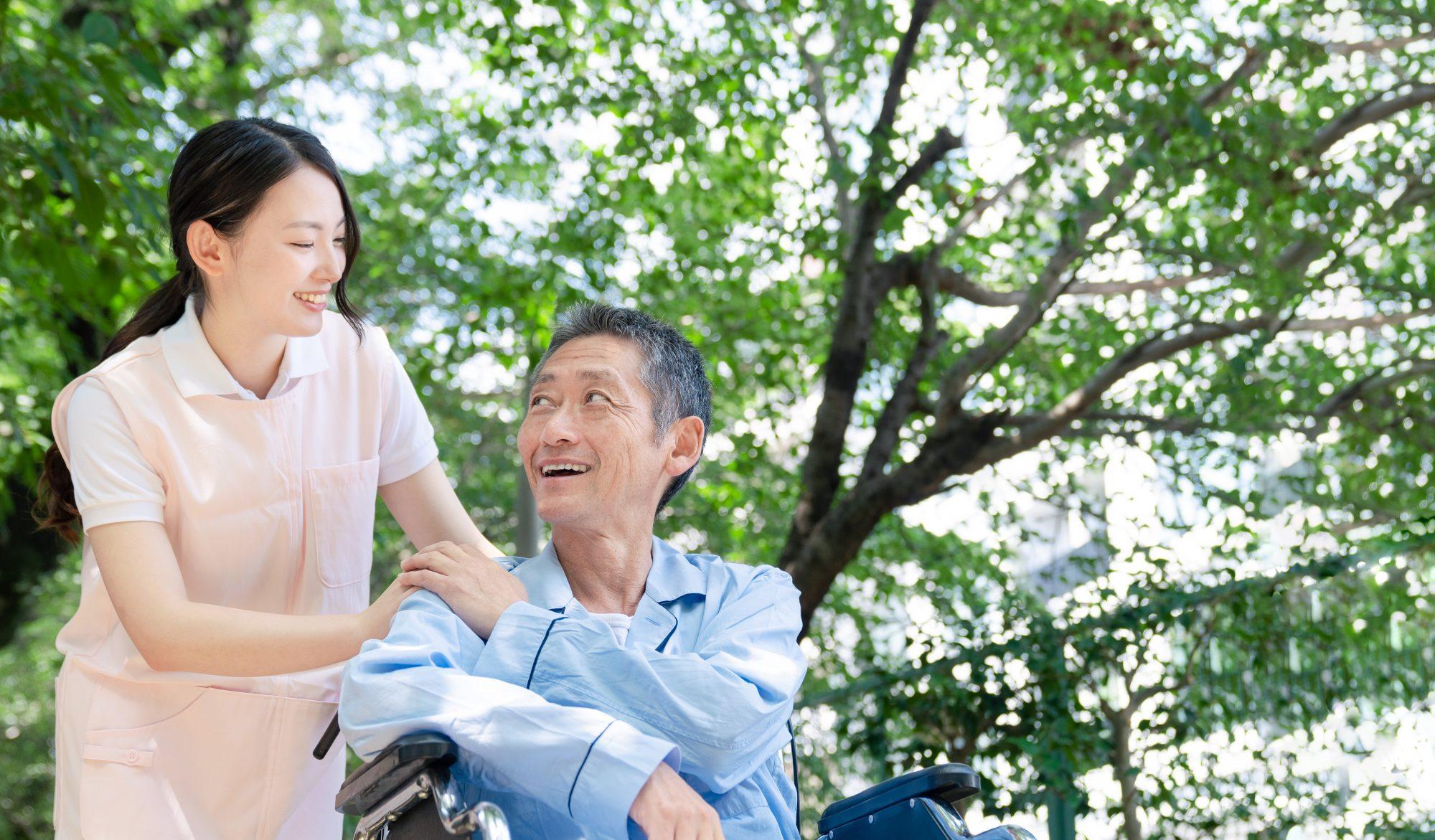車いすに乗った笑顔の老人男性と接する笑顔の女性介護士