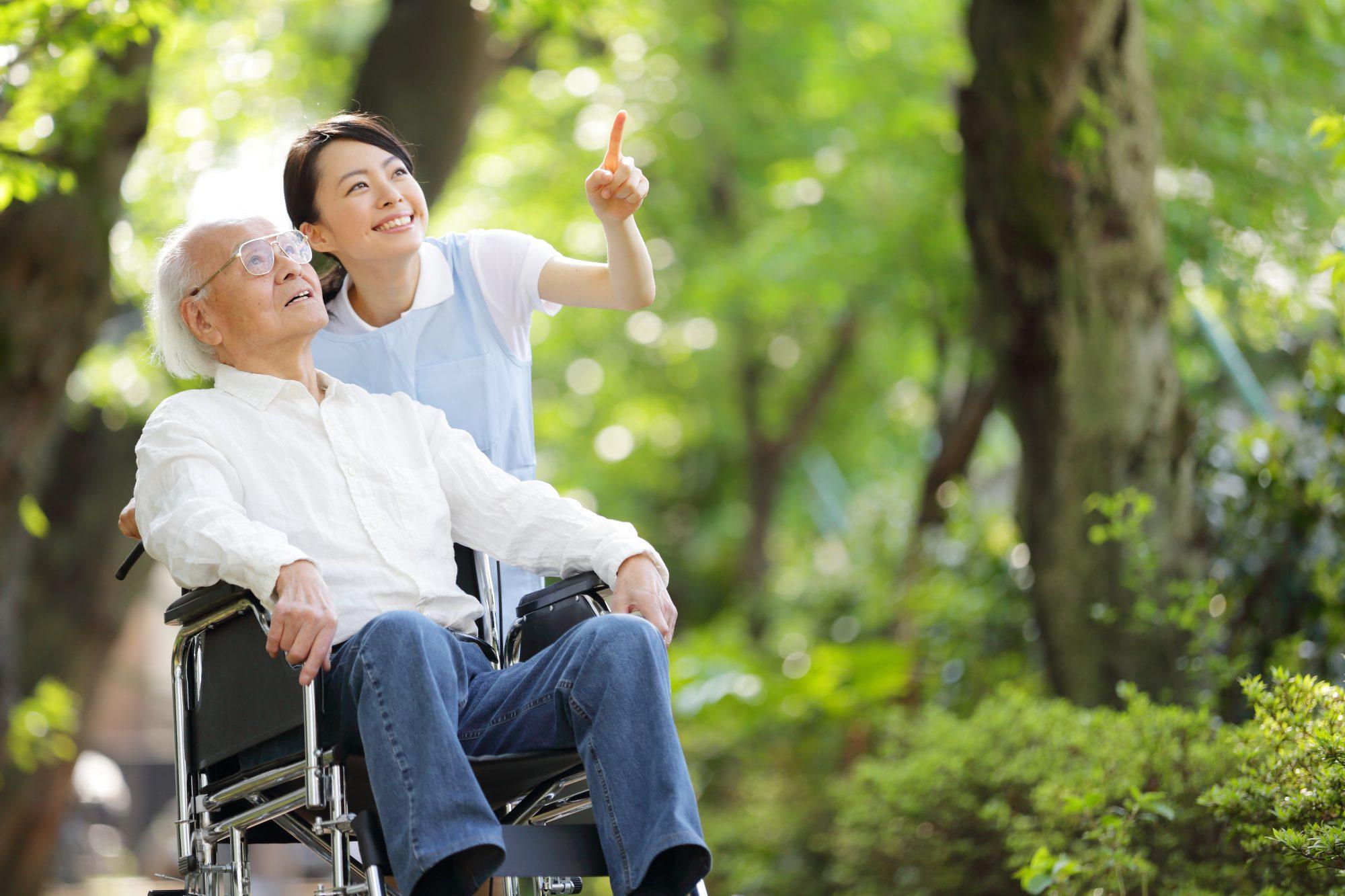 上を見上げる車いすの男性老人と笑顔で指をさす女性介護士