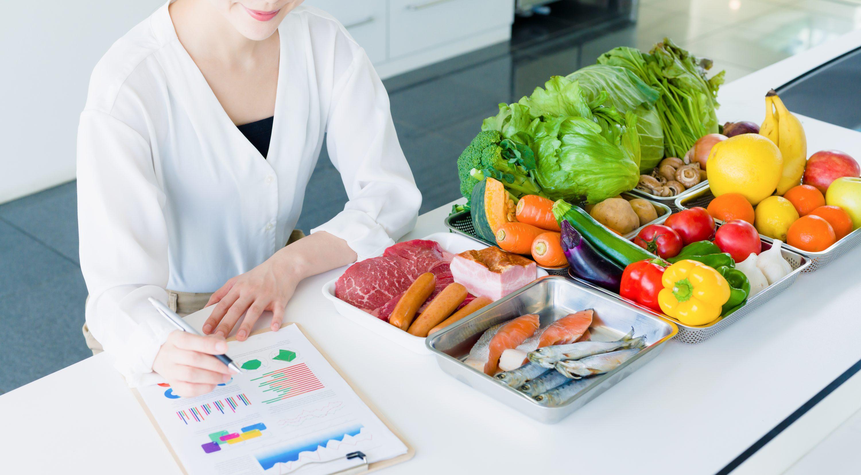 たくさんの食材が並んだテーブルで勉強している女性のイメージ