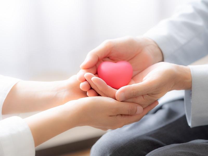 ハートの置き物を持つ高齢者の手を包み込む介護士の手