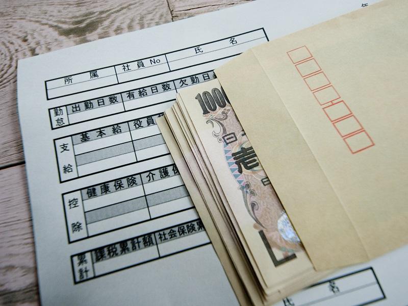 給与明細と1万円が入っている封筒のイメージ