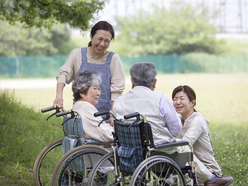車椅子の夫婦とヘルパー