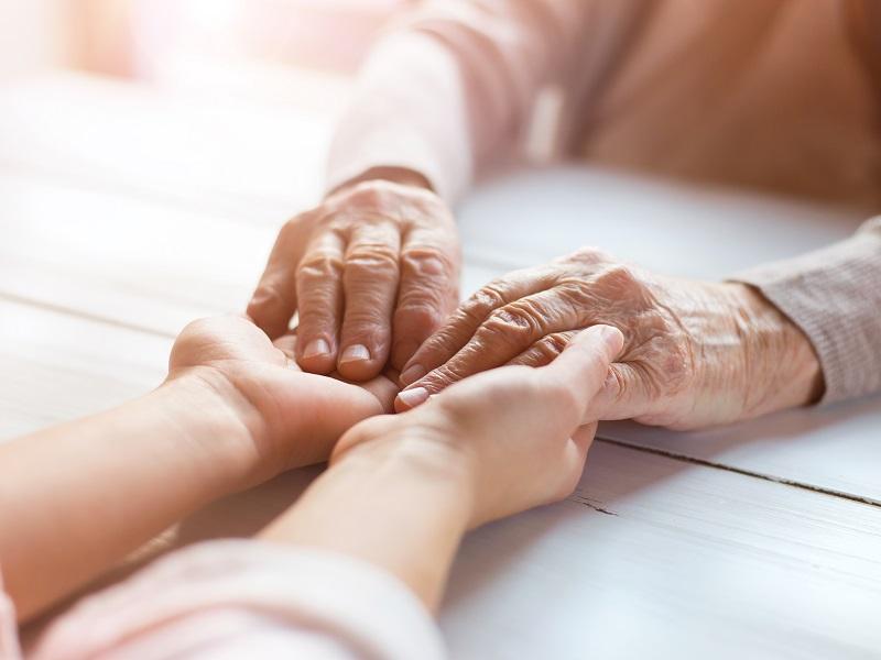 手を取り合うシニアと女性の画像