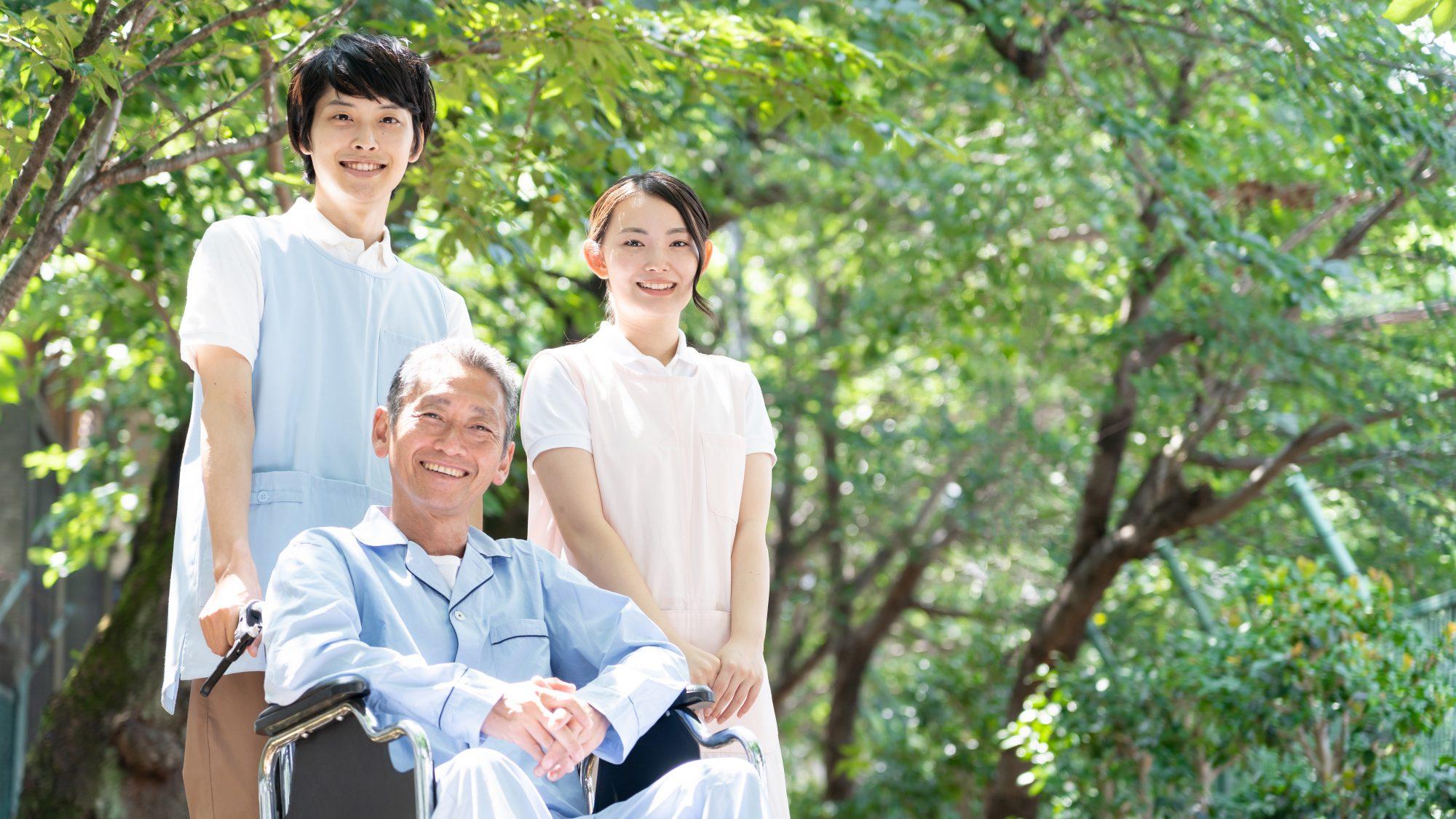 微笑む男女の介護士と車椅子に乗る男性の画像