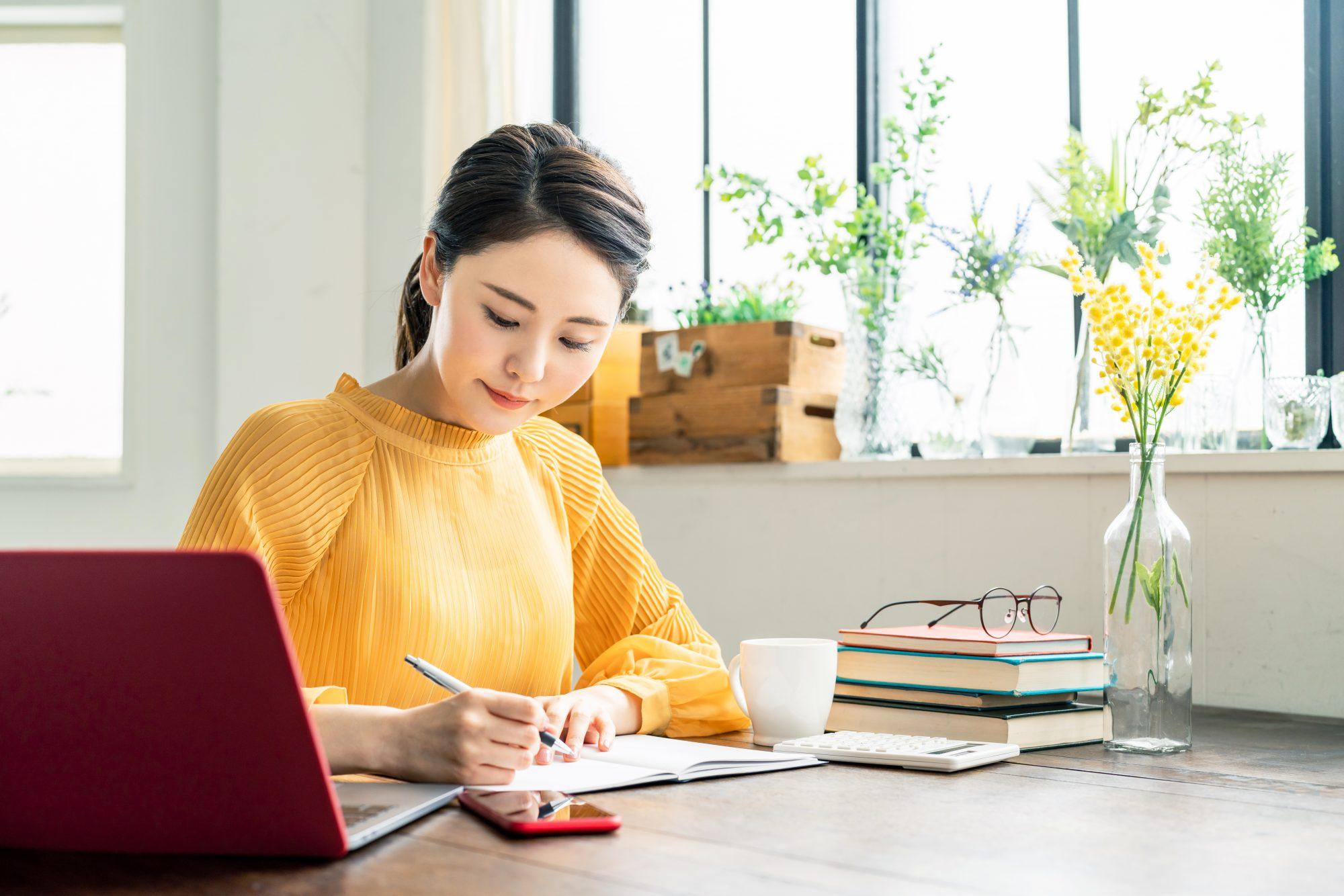 ノートパソコンと本に囲まれノートに書く作業をする女性の画像
