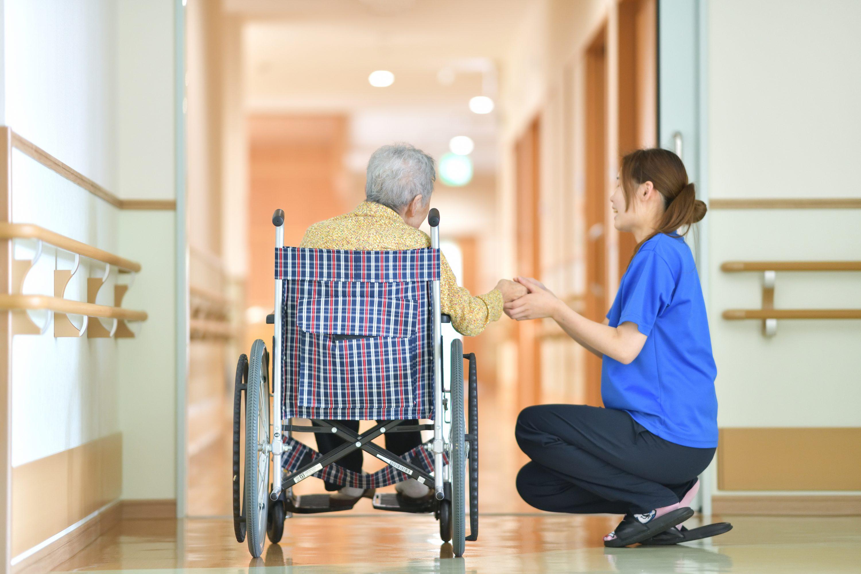 施設で車椅子の老人の手を握る女性スタッフの画像