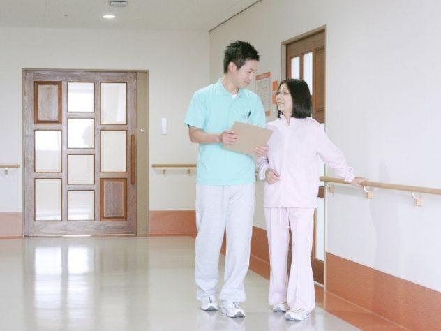高齢女性に寄り添って歩く介護スタッフ
