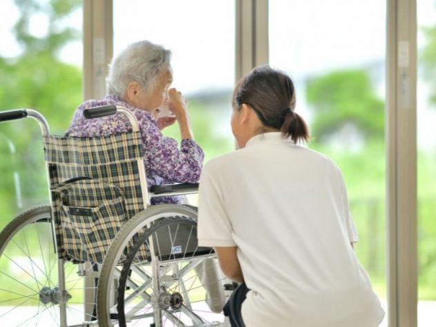 車椅子の高齢女性に寄り添って話をする女性スタッフ