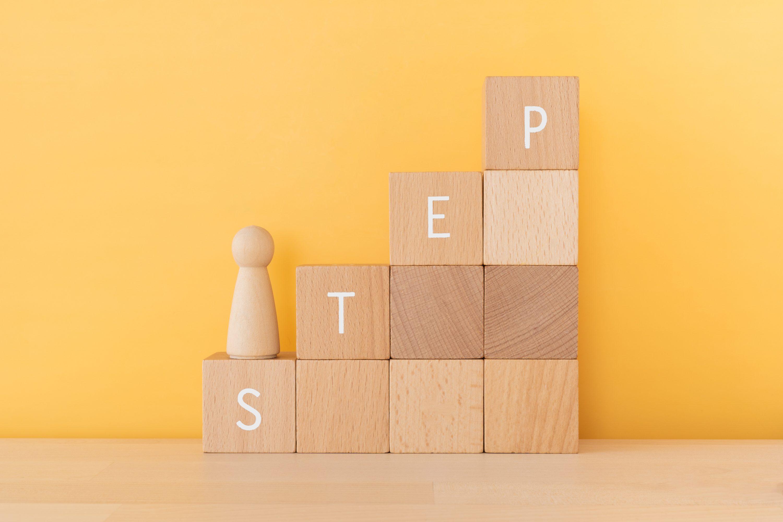 ステップと書かれた積み木と人形のイメージ
