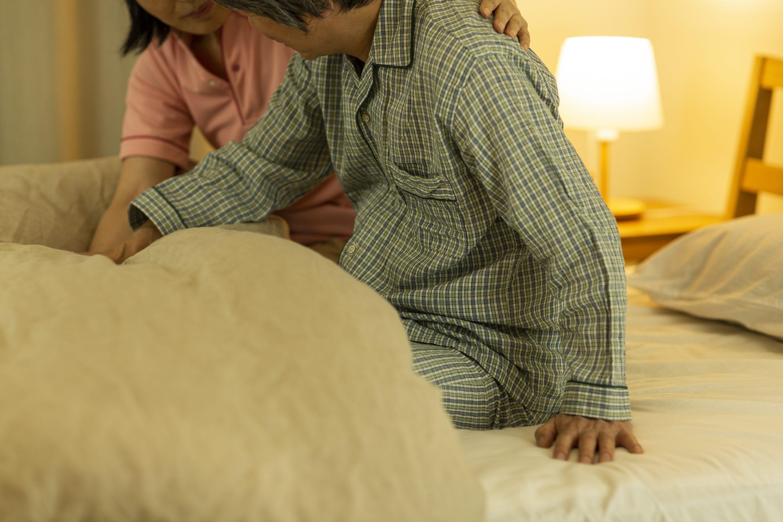 夜間にベッドで起き上がろうとする高齢者をサポートしている介護士のイメージ