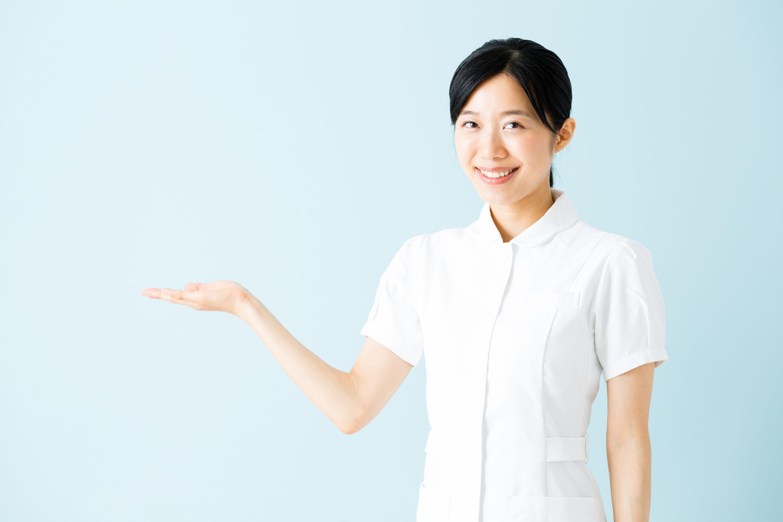 白い制服を着た介護士が微笑みながら紹介するポーズをしているイメージ