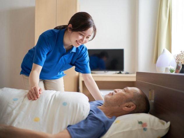 ベッドで横になる男性に寄り添う女性介護士の画像