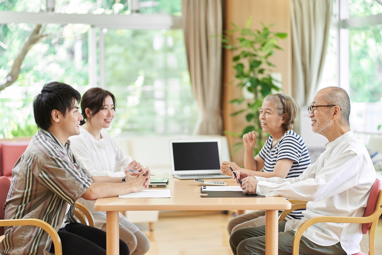 ケアマネージャーと笑顔で会話する高齢者夫婦のイメージ