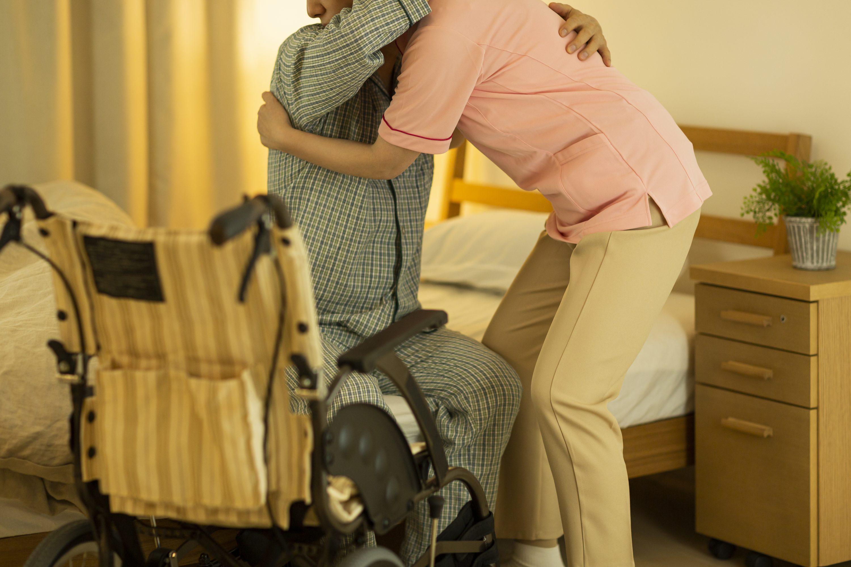ベッドから車椅子への移乗をサポートする介護士のイメージ