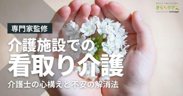 両手で白い花を包むように持つ画像